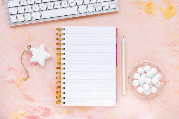 Notatnik, długopis, klawiatura komputerowa, zegar, czekolada na biurku