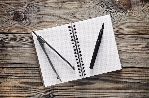 Notatnik, długopis, kompasy na drewnianym stole. widok z góry.