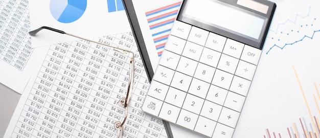 Notatnik, długopis, okulary i kieszonkowy kalkulator na białej powierzchni