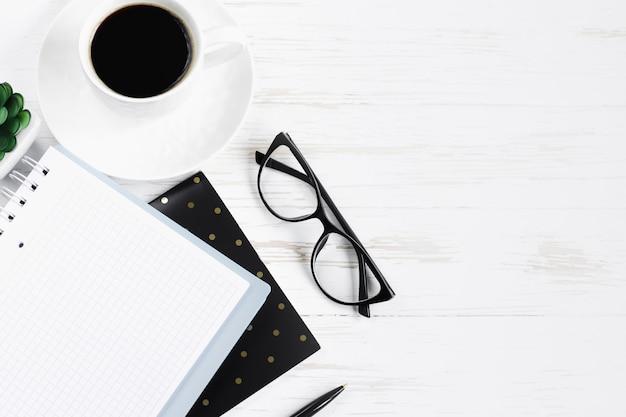 Notatnik, długopis, okulary, rośliny sukulenty, filiżanka kawy na białym drewnianym stole, leżał płasko, widok z góry. biurko na biurko, miejsce pracy