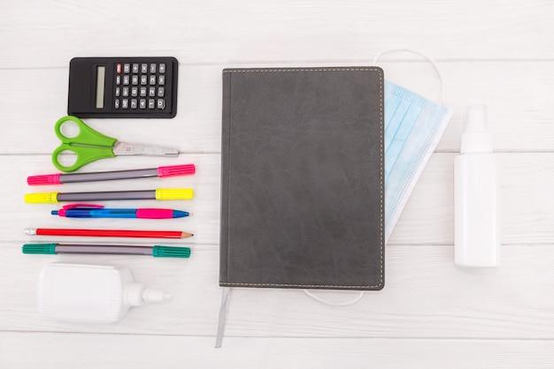 Notatnik, długopis, przybory szkolne i maska na białym