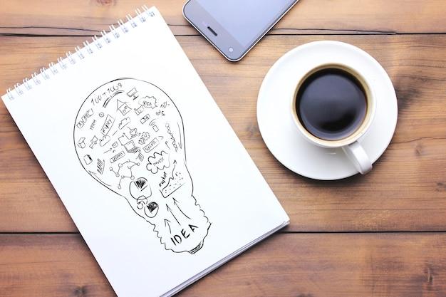 Notatnik, długopis, telefon i kawa na drewnianym stole