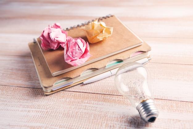 Notatnik, długopis, zmięte papiery i żarówka na stole