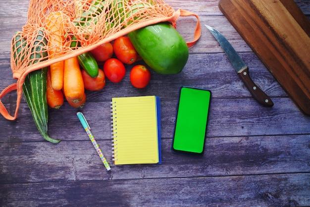 Notatnik do krojenia świeżych warzyw i smartfon na stole
