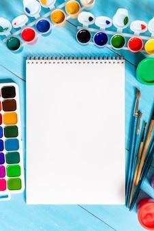 Notatnik do rysowania farbami i farbami wielokolorowymi na niebieskim tle. skopiuj miejsce.