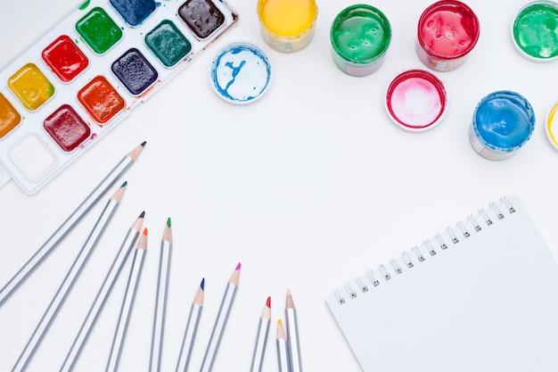 Notatnik, farby, ołówki na białym tle.