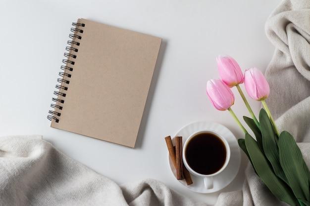 Notatnik, filiżanka gorącej kawy, szalik, tulipany na białej powierzchni. koncepcja wiosny. leżał płasko, widok z góry