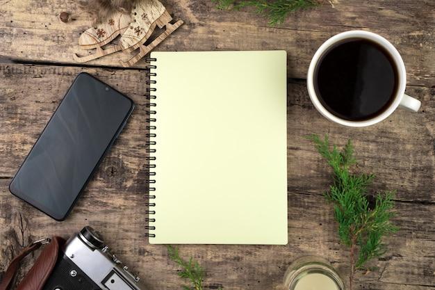 Notatnik, gałązki iglaste, kawa, telefon i aparat retro
