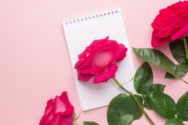 Notatnik i ciemnoróżowa róża na różowym widoku z góry