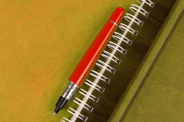 Notatnik i czerwony długopis leżący na drewnianym biurku. przedmioty do biura i edukacji