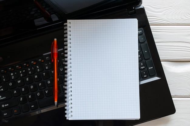 Notatnik i długopis leżący na klawiaturze laptopa