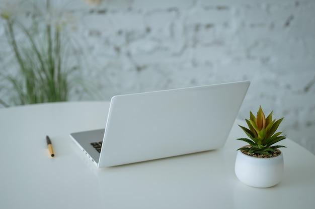 Notatnik i długopis na białym stole kwiaty w wazonie soft focus