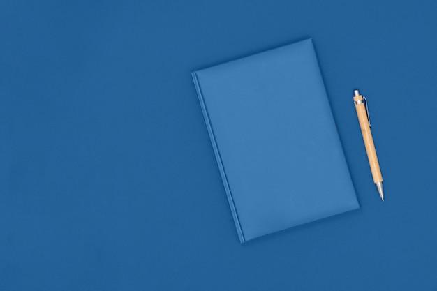 Notatnik i długopis na niebieskim stole. pomysł na biznes.