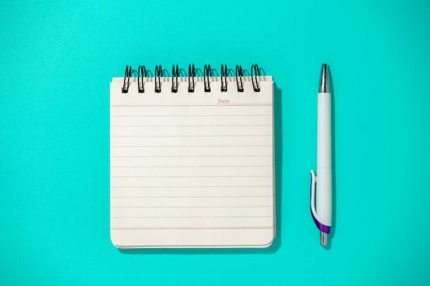 Notatnik i długopis na niebieskim stole