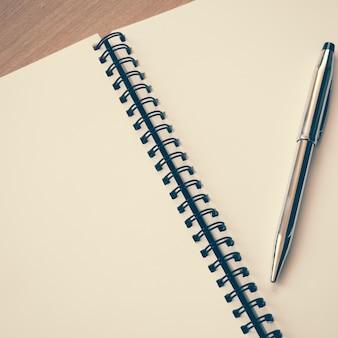 Notatnik i długopis na stole z filtrem efekt retro styl vintage