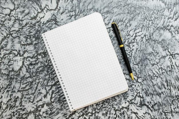 Notatnik i długopis na szarym tle z teksturą