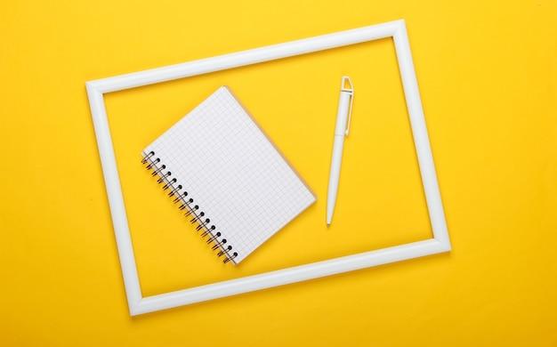 Notatnik i długopis na żółtej powierzchni z białą ramką