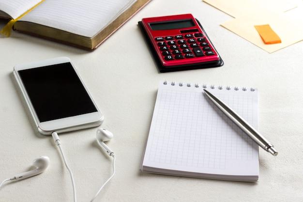 Notatnik i długopis, telefon i słuchawki, kalkulator. praca w domu.