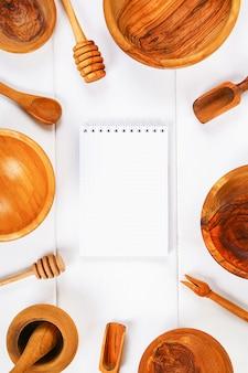 Notatnik i drewniany naczynie w kuchni na białym drewnianym tle z kopii przestrzenią.