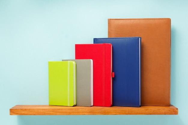 Notatnik i książka na półce na powierzchni tła ściany