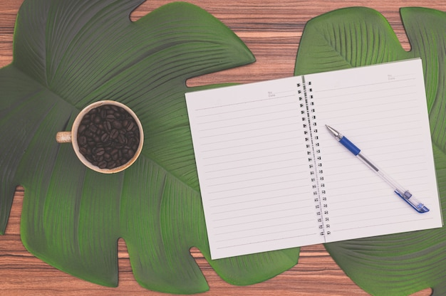 Notatnik i kubek do kawy na biurku