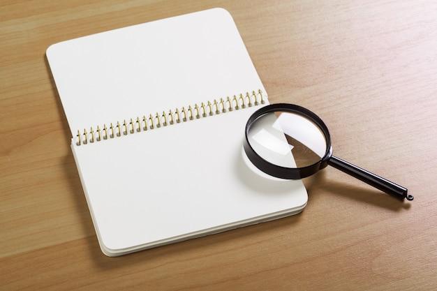 Notatnik i lupa na drewnianej powierzchni