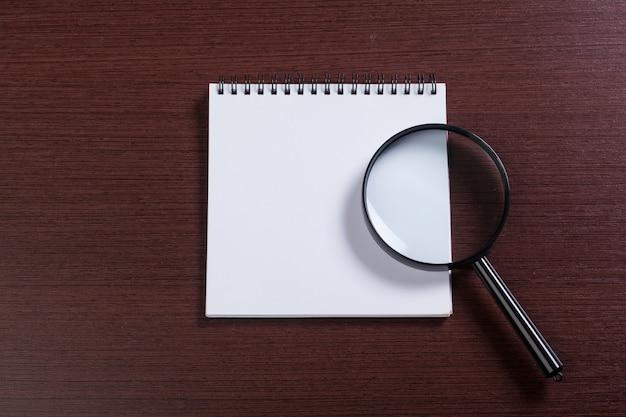 Notatnik i lupa na drewnie