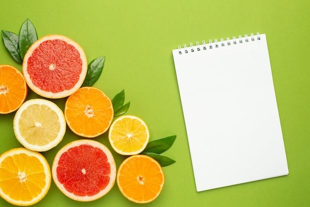 Notatnik i owoce cytrusowe, płaska owocowa, minimalna letnia kompozycja z grejpfruta, cytryny, mandarynki i pomarańczy. kolor letni, zbiór, krojenie owoców