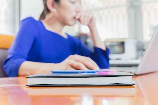 Notatnik i pióro na stole z kobietą woking na laptopie w plamy tle.