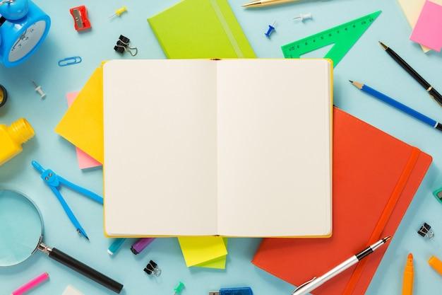 Notatnik i przybory szkolne na abstrakcyjnej powierzchni tła