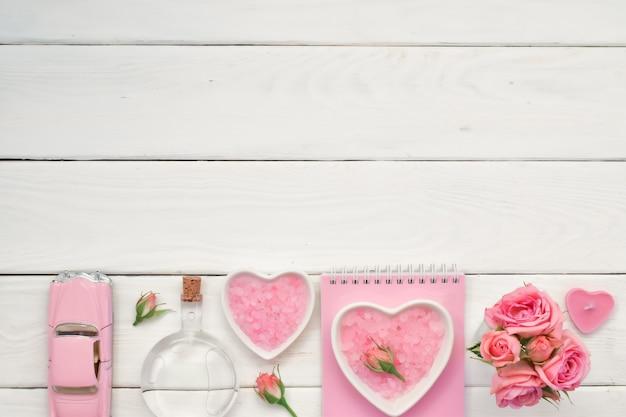 Notatnik i różowe róże na białym drewnianym stole z miejscem na tekst sole do kąpieli i perfumy pusta przestrzeń płaski leżał widok z góry