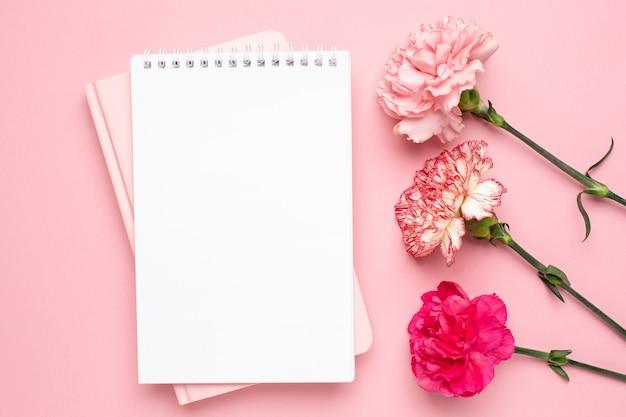 Notatnik i różowy kwiat goździka na różowym tle