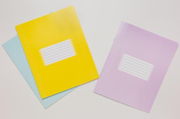 Notatnik i zeszyt na biurku. makiety w biurze kopii przestrzeni na białym tle. powrót do szkoły