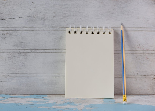 Notatnik i żółty ołówek na tle starodawny niebieski drewniany stół
