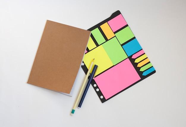 Notatnik, kolorowe naklejki, ołówek i długopis