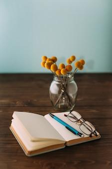 Notatnik, kwiaty, długopis i okulary.