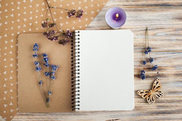 Notatnik, kwiaty lawendy, świece i drewniany motyl