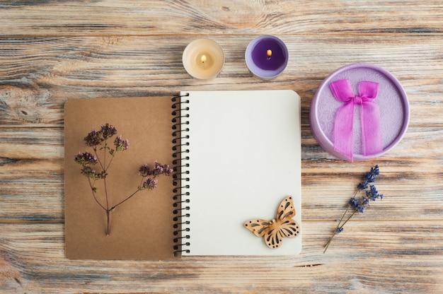 Notatnik, kwiaty lawendy, świece, motyl