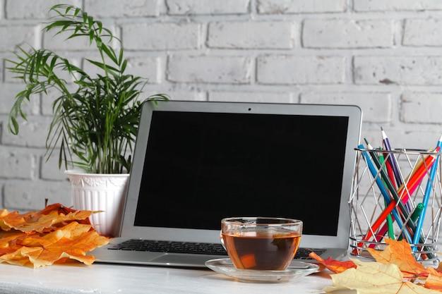 Notatnik, laptop, kwiaty i jesienne liście. widok z góry na białej ścianie. jesień leżała płasko. makiety dzieł sztuki w miejscu pracy