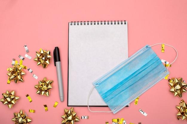 Notatnik listy życzeń z markerem leży na niebieskim tle ze złotym konfetti