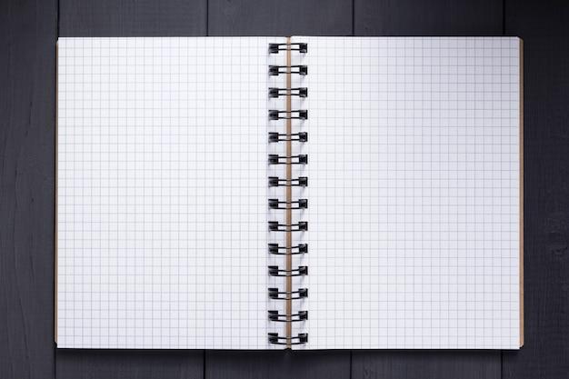 Notatnik lub notatnik na czarnym drewnianym stole z powierzchnią tła, widok z góry