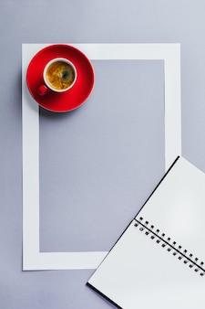 Notatnik lub szkicownik, czerwony kubek z kawą i ramą papieru na klasycznym niebieskim stole