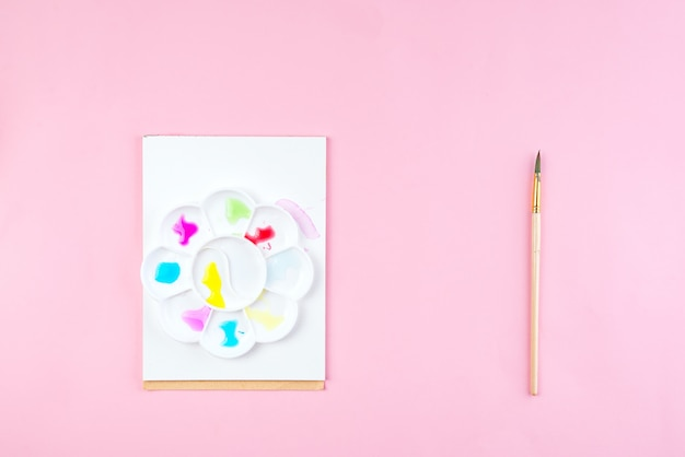 Notatnik makiety do grafiki z farbami akwarelowymi, palety i pędzle.