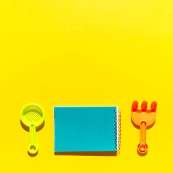 Notatnik miarka i grabie na kolorowej powierzchni
