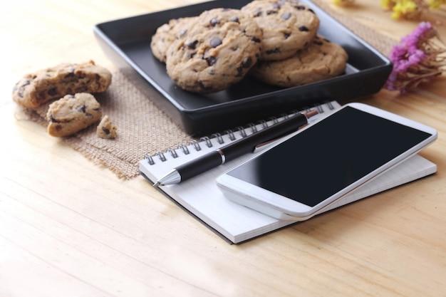 Notatnik na biurku z kawowym ciastkiem i piórem