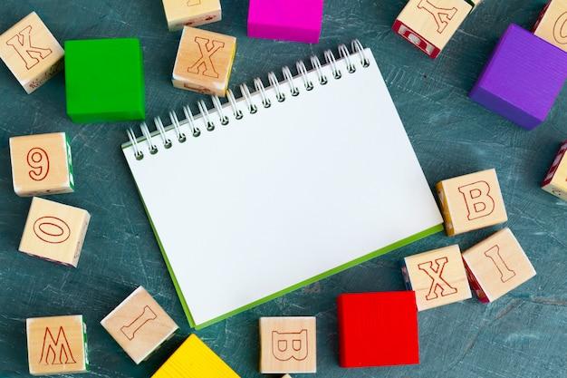 Notatnik na drewnianym stole i drewniane klocki alfabetu