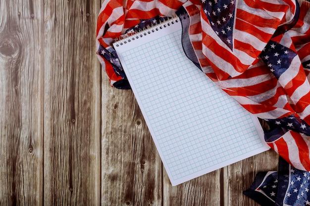 Notatnik na drewno stole pięknie macha gwiazdę i paski amerykańską flagę na tle