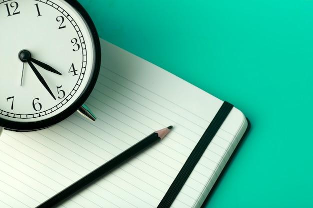 Notatnik na karteczki na biurku z budzikiem. pulpit biurowy, koncepcja zarządzania i synchronizacji.