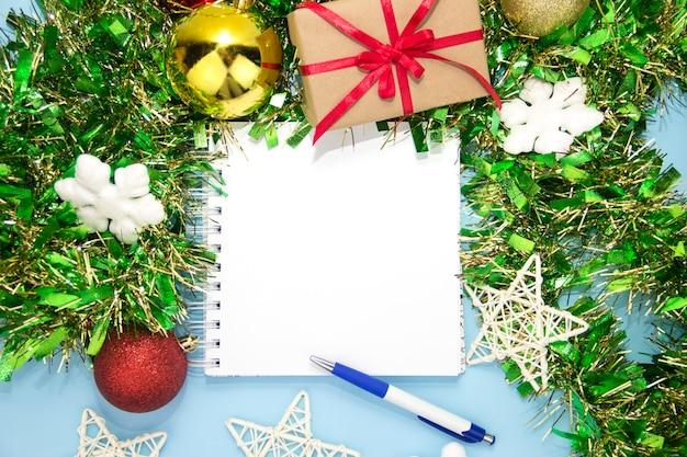 Notatnik na notatki z długopisem i ozdobami świątecznymi. nowy rok niebieskie tło. miejsce na tekst. tło nowego roku. boże narodzenie. kolęda. czysty otwarty notatnik, prezenty świąteczne