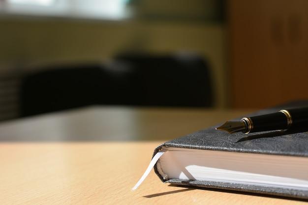 Notatnik na okładce pulpitu i piórze